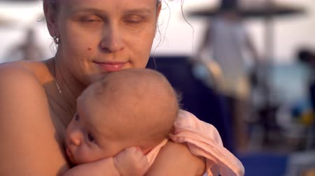 wistful : Slow motion shot of a woman daydreaming when relaxing at the beach with baby daughter. She holding child in hands and kissing her Stock Footage