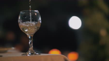 şarap kadehi : Cinemagraph - close-up shot of pouring white wine into the glass in outdoor restaurant at night, blurred lights in background