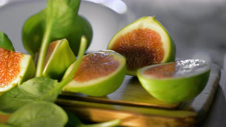 fig : Close-up shot of cut green figs on wooden board with falling fresh basil leaves Stock Footage