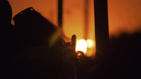 čelo : Slow motion shot of black silhouette of unidentified long-haired woman with sunglasses on forehead against the sunset in orange evening sky Dostupné videozáznamy