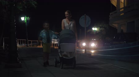 outing : Woman with elder son and baby carriage walking in the evening street, cars driving on the road alongside