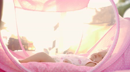 portátil : Slow motion shot of a baby girl moving hands and legs when lying in pink bassinet outdoor, view against bright summer sunshine Vídeos