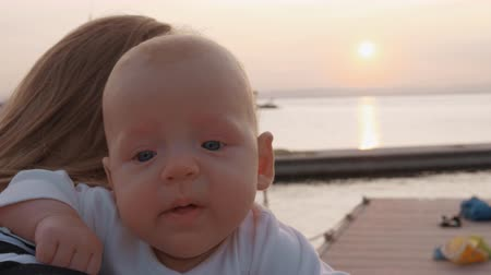 hónapokban : Baby girl making different face expressions being in mothers hands and looking to the camera. Outdoor shot on the pier at sunset