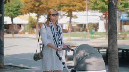 kareta : Young woman in sunglasses having a walk with baby on summer day. Mother pushing baby carriage along the street