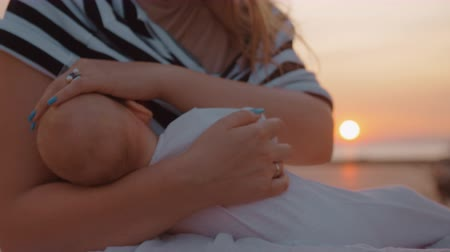 szoptatás : Mother nursing baby daughter and stroking her head gently. Outdoor shot with sunset in background