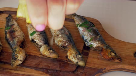 основное блюдо : Close-up shot of woman squeezing lemon juice on grilled sardines served on wooden board
