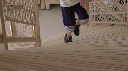 mandzsetta : Boy with foot drop system walking upstairs indoor. Child getting therapy with functional electrical stimulation