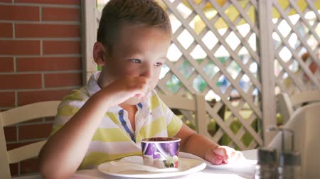 golosa : Slow motion shot of a boy enjoying sweet chocolate ice-cream in cafe on summer day