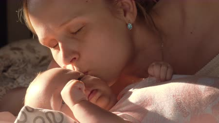 кавказский : Slow motion shot of a loving mother gently kissing baby daughter when they lying together on bed, view in bright sun light Стоковые видеозаписи