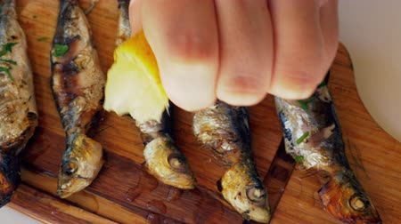 squeeze : Close-up shot of grilled sardines served on wooden board. Woman pouring fish with lemon juice before eating