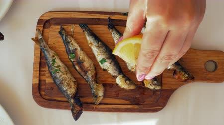 основное блюдо : Close-up shot of a woman pouring grilled sardines with lemon juice. Fish served on wooden board Стоковые видеозаписи