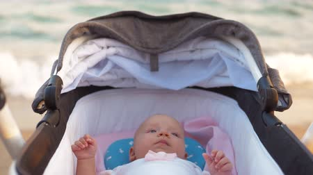 outing : Three months baby girl lying in pram at the beach. Sea in background. Outing with child at the seaside