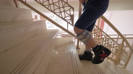 manşet : Slow motion shot of a boy with foot drop system walking upstairs indoor. Stok Video