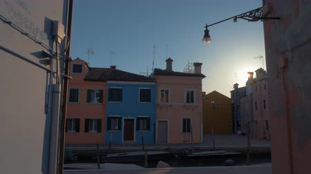 waterways : Street view in Burano island at sunset, Italy. Colorful houses on canal waterfront