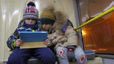 pedleri : Timelapse shot of two kids in winter clothes using digital tablet when traveling by trolleybus in evening city Stok Video