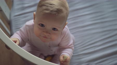 baby infant : A top view of a smiling baby girl in pink clothes, sitting in a crib and looking up with big beautiful eyes. She is holding the railing and trying to stand up