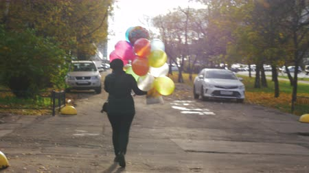 így : A slow motion view of a woman from a back who is walking down the street with colorful balloons in right hand. It is autumn, so there are lots or yellow leaves around