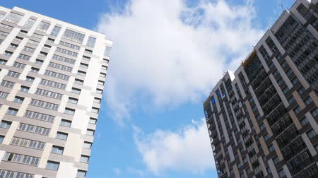inacabado : Low angle shot of new-built block of flats and unfinished apartment house against the blue sky with white clouds. Housing development Stock Footage