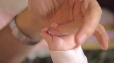 close up shot : Slow motion close-up shot of baby holding tight mothers finger. Mum and child bonding Stock Footage