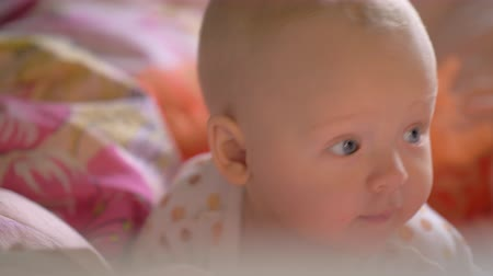 hazugság : A closeup of a cute baby girl with bright grey eyes. She is lying on stomach on colorful sheets and looking around, slightly smiling Stock mozgókép