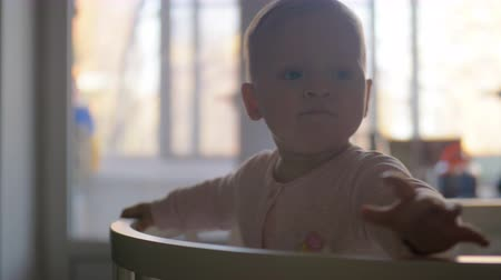 eleven people : Eleven months old baby girl standing in crib at home. Home portrait of lovely blue-eyed child Stock Footage