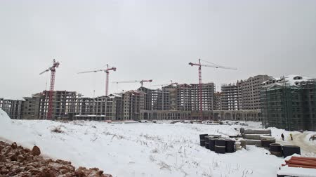 unfinished : Timelapse shot of apartment complex under construction . Winter view with working cranes, Russia