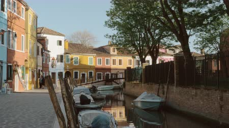 waterways : Picturesque scene of Burano island, Italy. View to the canal with moored boat and brightly painted houses