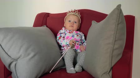 eight : Eight months baby girl wearing a crown and looking like a little princess. Child with wand in big red armchair