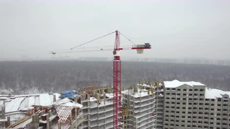 unfinished : Flying over construction site with multistorey apartment complex. Winter view with unfinished building and crane, Russia Stock Footage