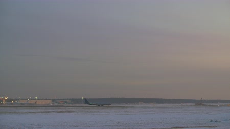 odejít : Airport with one plane start taxiing while another is taking off. View in winter evening, Russia
