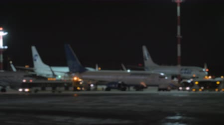 el feneri : Blue and white airplanes are standing on an airport courtyard against dark night sky. Some service cars and buses are driving among them, flashing with lights