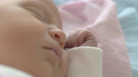 így : A closeup of a baby girls cute face who is sleeping, lying on her side. Her hand is close to the face so every tiny fingernail can be seen
