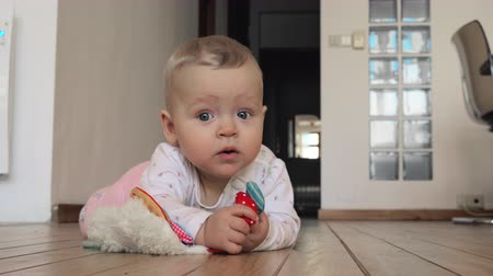eight : Lovely quiet baby of eight months old lying on the floor at home. Blue-eyed child holding soft toy in hands and smiling