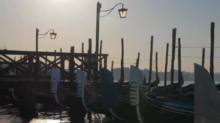 romance : Slow motion shot of several moored gondolas swinging on water at the dock, view at sunset with wooden pier. Venice, Italy