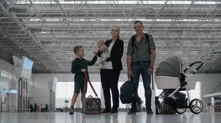 Happy family of four at the airport. Cheerful parents and children waiting for the flight. Elder son playing with baby in mothers hands Stok Video