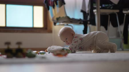 osm : Baby girl at home. Eight months child crawling on the floor being attracted with the toys