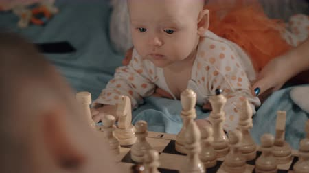 ロジック : Mother playing chess with elder son and baby daughter crawling on the bed and looking at chess figures