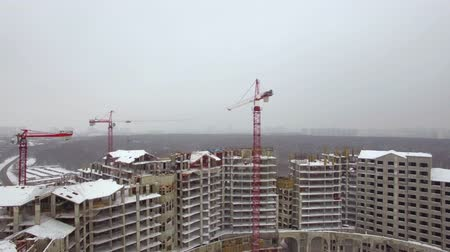 inacabado : Flying over construction site in suburban bedroom community. Unfinished apartment complex and cranes. Winter view, Russia Stock Footage
