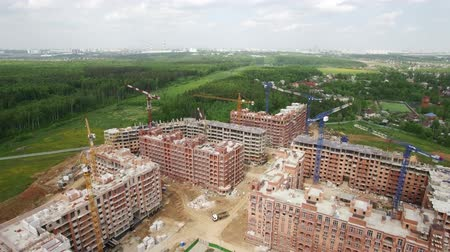 kusy : Flying over residential area with new built apartment blocks and unfinished houses among green woods. New Moscow area in Russia, spring view