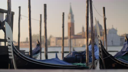 waterways : Moored gondolas swinging on water. Church of San Giorgio Maggiore with Bell Tower in background. Venice view, Italy Stock Footage