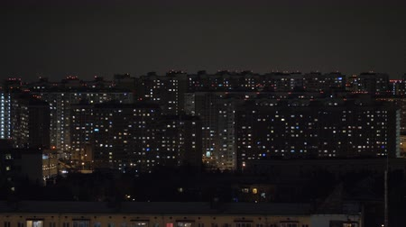 built up : Night cityscape with lots of highrise apartment blocks. Window lights illuminated in the darkness, panning shot. Moscow, Russia