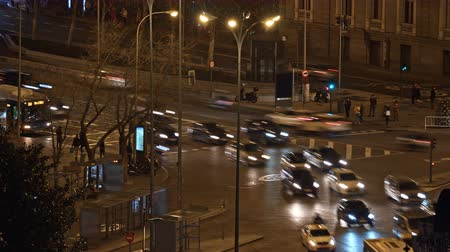 junção : Timelapse shot of busy street in night Madrid, Spain. Stream of car traffic and pedestrians crossing the road Vídeos