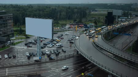 interscambio : Timelapse shot of car traffic on multilevel crossing. City view with hotel, parking lot and blank banner on rainy day