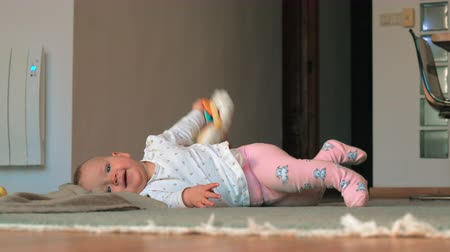 колготки : A baby girl in white shirt and pink tights is lying on a floor. She is holding a toy sheep in hands, smiling and then trying to turn on a stomach. After this unsuccessful attempt she is turning on back to continue to play