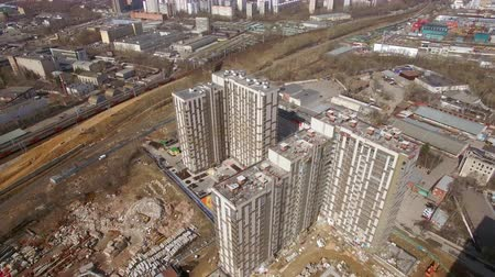 unfinished : Aerial shot of modern highrise apartment complex under construction near the railroad, spring view. Moscow, Russia