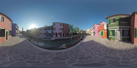 waterways : 360 VR video. Burano island in Italy. Scene with paved streets and traditional colourful houses along the canal with moored boats. View with Leaning Bell Tower and bright sunshine
