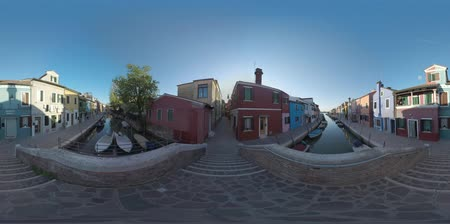 水路 : 360 VR video. Looking at Burano from the footbridge. Traditional painted houses, narrow alleyways and boats moored along the canal. Quiet scene of popular touristic destination in Italy