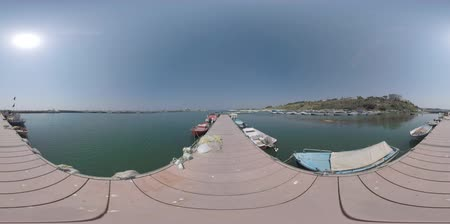 dockyard : 360 VR video. Scene of the harbour with boats tied up and hotel on the coastal hill. Man walking on the pier with fishing nets lying near the vessels. Nea Kallikratia, Greece