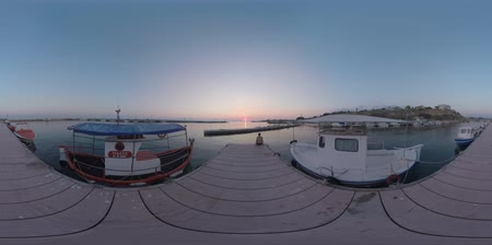mooring : 360 VR Video. Marine scene with harbour and boats tied up. Man sitting on the pier and looking at sunset over the sea. Nea Kallikratia, Greece Stock Footage