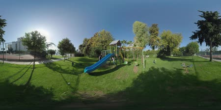 ferret : 360 VR video. Happy dad and son having fun on the playground. Child going down a slide and playing tag with father. Green area with sports ground near the hotel in Turkey, Antalya Vidéos Libres De Droits